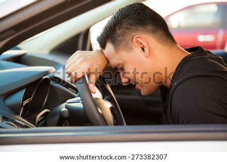 Profile view of a young man leaning on the steering wheel and feeling stressed and upset