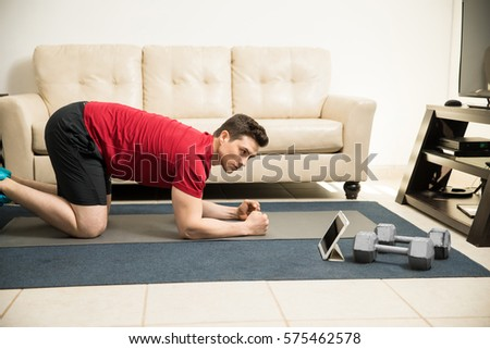 Profile view of a young man looking at a training routine on a tablet computer while exercising at home
