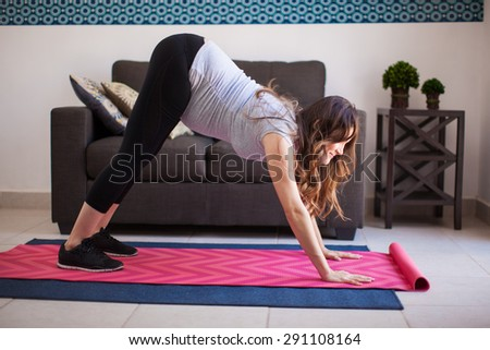 Profile view of a young pregnant woman trying the downward dog yoga pose at home - stock photo