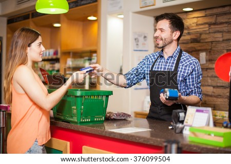 Profile view of a young woman paying with a credit card to a store clerk in a supermarket - stock photo
