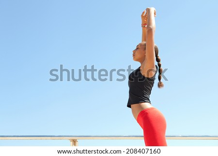 Profile view of an athletic and sporty young african american black woman stretching her legs and body while exercising on a sunny day against a bright blue sky. Sport active lifestyle outdoors. - stock photo