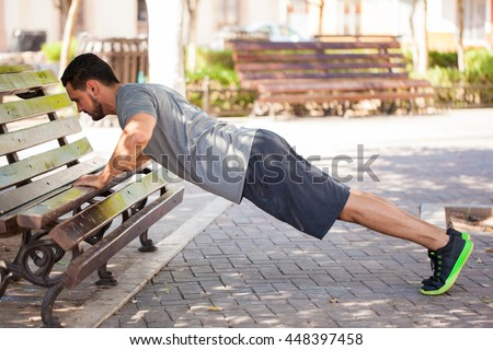 Profile view of an athletic young man exercising outdoors in a park and doing push ups on a park bench