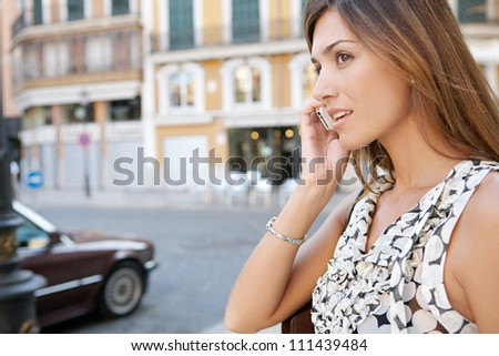 Profile view of an attractive businesswoman having a phone conversation in a classic city with traffic. - stock photo