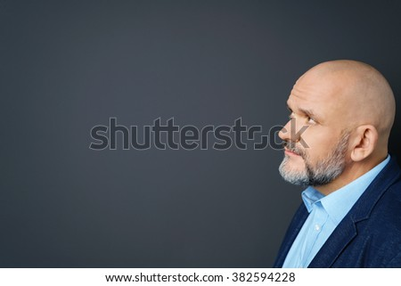 Profile view of an attractive thoughtful middle-aged man with a goatee staring at blank copyspace on a dark background with a pensive frown - stock photo