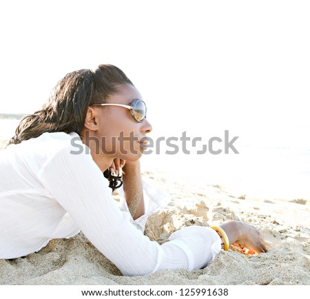 Profile view of an attractive young african american black woman contemplating the ocean while relaxing on a white sand beach on vacations. - stock photo