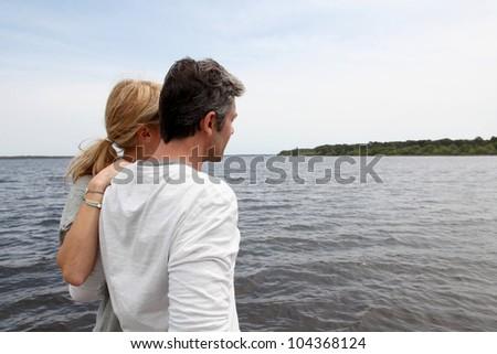 Profile view of couple sitting on a wooden bridge by a lake - stock photo