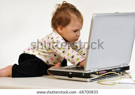 Profile view of cute multi racial toddler looking attentively at laptop display and playing with the keyboard.