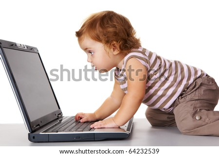 Profile view of cute toddler looking attentively at laptop display