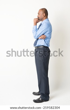 Profile view of full body Indian businessman hand on chin looking at blank copy space, standing on plain background with shadow - stock photo
