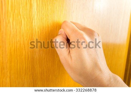profile view of hand knocking the wooden door - stock photo