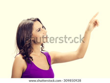 Profile view of happy smiling beautiful young woman in casual smart lilac clothing, showing copyspace, visual imaginary or something, or pressing virual button - stock photo