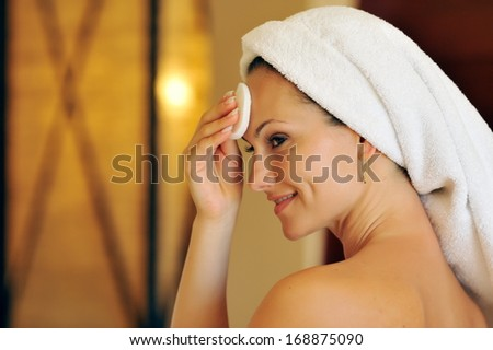 profile view of happy young woman cleansing her face - stock photo
