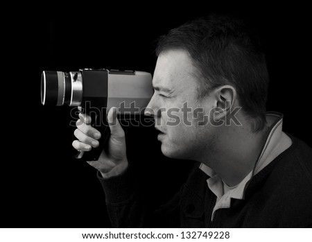 profile view of man with cine film / video camera. black and white landscape - stock photo