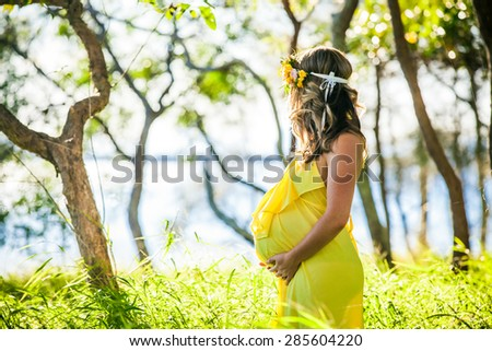 Profile view of pregnant woman with long hair in yellow dress in the park - stock photo