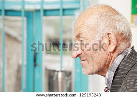 Profile view of senior man sitting against window - stock photo