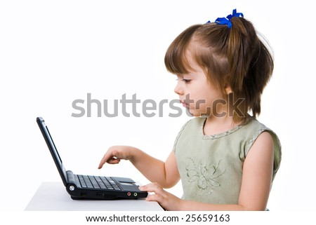 Profile view of serious preschooler going to push Enter button on laptop keyboard