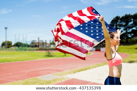 Profile view of sportswoman raising an american flag against athletics field on a sunny day
