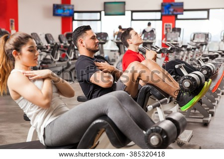 Profile view of two men and a woman doing crunches and working on their abs at the gym - stock photo