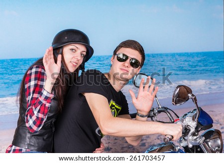 Profile View of Young Couple on Motorcycle at Beach Waving to Camera