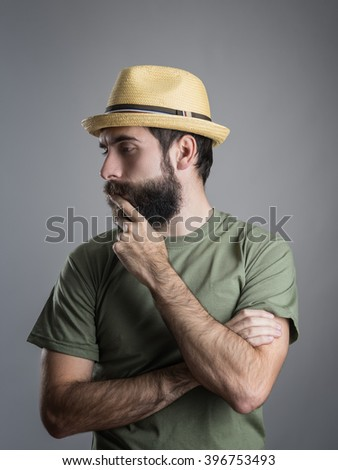 Profile view of young pensive bearded man wearing straw hat touching his beard. Headshot portrait over gray studio background with vignette.