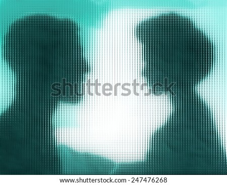 Profiles of man and woman behind blue glass - stock photo