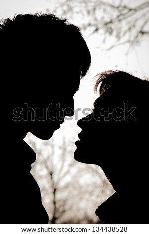Profiles of romantic couple looking at each other - stock photo