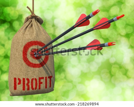 Profit - Three Arrows Hit in Red Target on a Hanging Sack on Green Bokeh Background. - stock photo