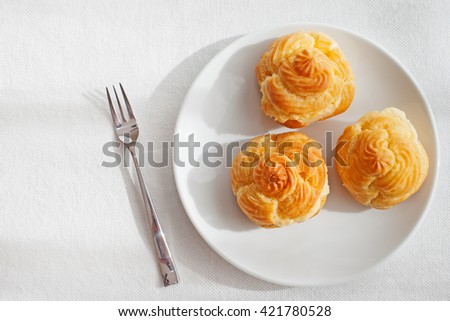 Profiteroles, choux with a custard cream, creme anglaise, whipped cream, dessert on a white plate Copy space Top view - stock photo