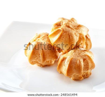 profiteroles on plate close-up isolated on white background - stock photo