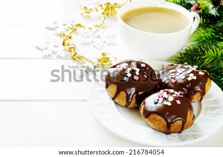profiteroles with chocolate icing and colored powder and cup of coffee on a light wood background. tinting. selective focus on the top of front profiterole - stock photo