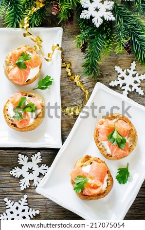 profiteroles with salmon and cream cheese on a dark wood background. tinting. selective focus on parsley on the middle profiterole - stock photo