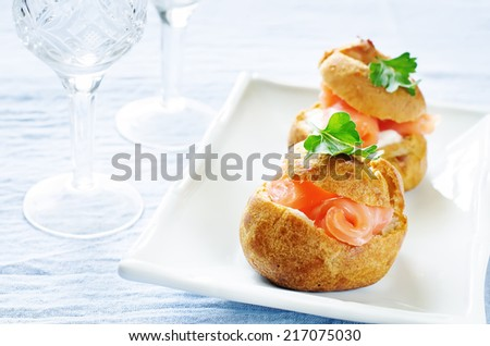 profiteroles with salmon and cream cheese on a light blue background. tinting. selective focus on parsley - stock photo
