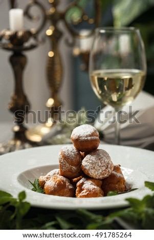 Profiteroles with whipped cream and powdered sugar on a table with candles and white wine