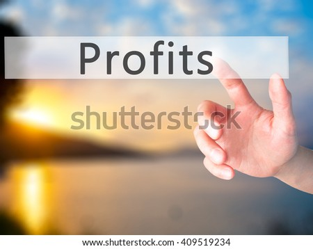 Profits - Hand pressing a button on blurred background concept . Business, technology, internet concept. Stock Photo