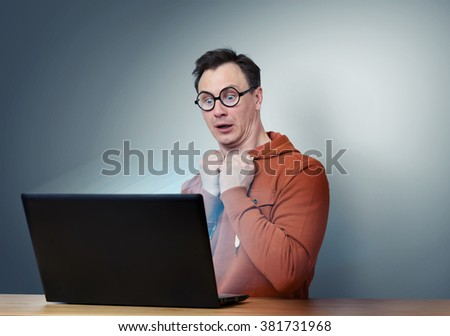 Programmer in glasses with laptop. Deep Fear - stock photo