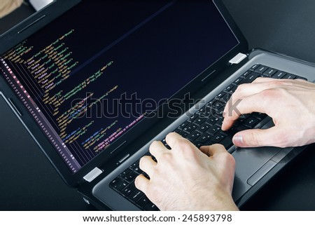 programmer occupation - writing programming code on laptop - stock photo