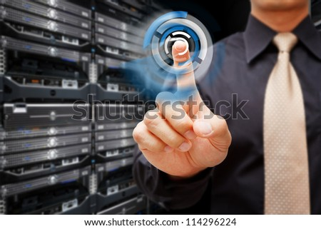 Programmer press on power button in data center room - stock photo