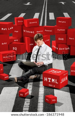 Programmer sitting and working with laptop on the asphalt road surrounded with red boxes with different programming languages - stock photo