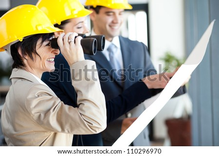 project manager looking at construction site with binoculars - stock photo