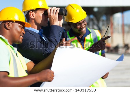 project manager using binoculars looking at the construction site with workers - stock photo