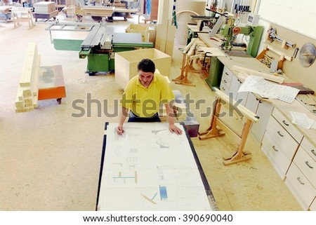 Projecting of a new house drawings. Professional carpenter planning a new building for a client within a industrial factory. Conceptual study for interior design. View from above. - stock photo