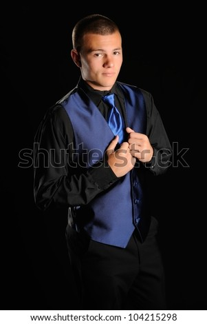 Prom Fashion. Teenage boy posing for a portrait in a black tuxedo with blue accents in front of a black background.