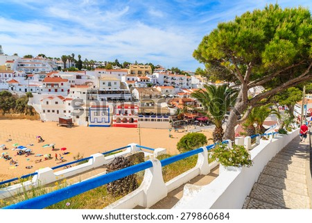 Promenade along street in Carvoeiro fishing village with view of colourful houses on beach, Algarve, Portugal - stock photo