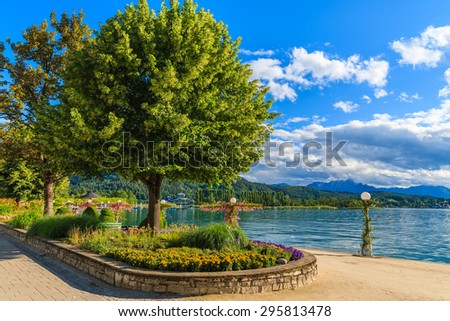 Promenade with flowers along Worthersee lake on beautiful summer day, Austria - stock photo