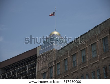 Prominent downtown building in San Antonio Texas with a golden dome flying the state flag - stock photo