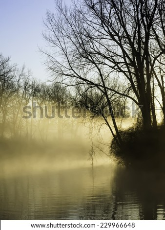 Promise of peaceful illumination: Rays from rising sun light up morning mist over a quiet river early in northern spring - stock photo