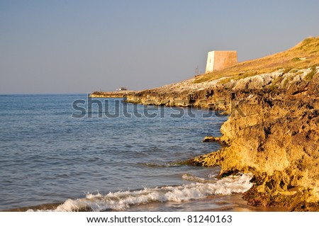 Promontory on the rocky coast near Peschici with an ancient Torre Saracena, typical lookout tower of the coast of Gargano. - stock photo