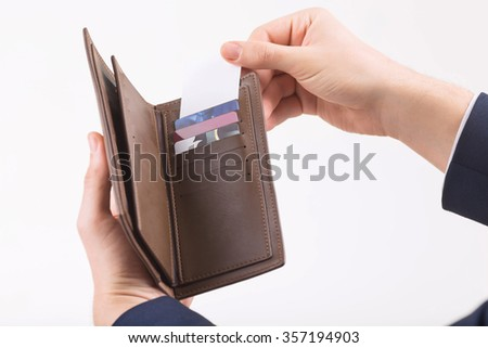 Promotional card. Male hand putting business card into the wallet.