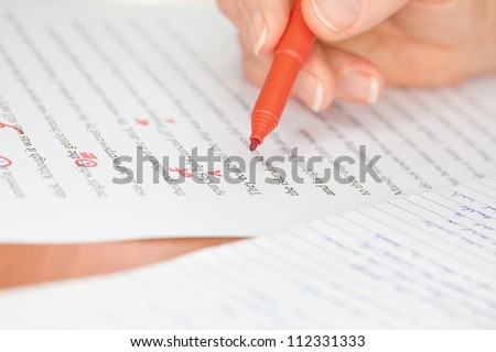 Proofreader with red pen checks a transcribed page