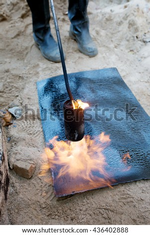 Propane blow torch flame and melting insulation material during waterproofing works basement concrete wall - stock photo